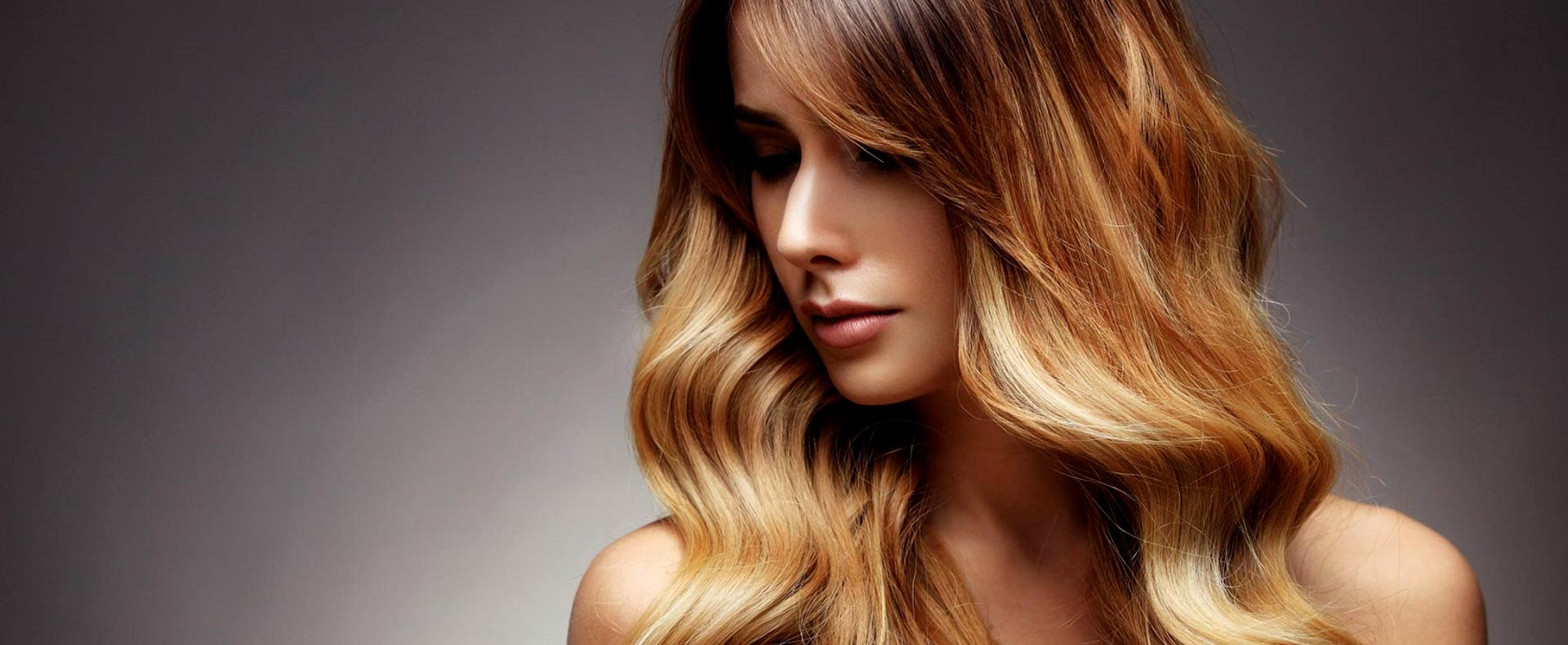 Hier zu sehen ist eine Frau mit gewellten Haaren im Ombre Look- Friseur Hair&Style Altbach