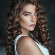 Hier zu sehen ist eine Frau mit gelockten Haaren und helleren Strähnen in braunem Haar | Trend Haarfarben 2020 - Hair&Style Altbach