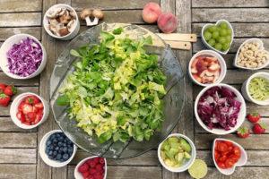 Hier zu sehen ist eine Salatschüssel umringt von kleineren Schüsseln mit Obst und Gemüse für eine gesunde Ernährung | Tipps gegen fettige Haare - Hair&Style Altbach