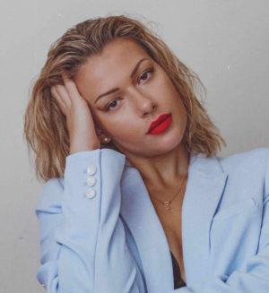 Hier zu sehen ist eine Frau in einem Blazer, die Sleek Back Hair als Frisur für fettige Haare trägt | Tipps gegen fettige Haare - Hair&Style Altbach