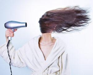 Hier zu sehen ist eine Frau im Bademantel, die ihre Haare stylt und dabei ins Gesicht föhnt | Tipps gegen fettige Haare - Hair&Style Altbach