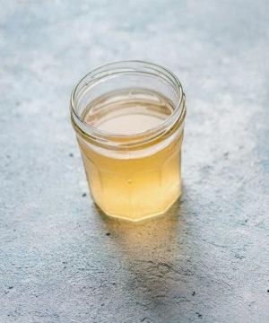 Hier zu sehen ist ein Glas Apfelessig, das als Hausmittel gegen Schuppen hilft | Was hilft gegen Schuppen Tipps & Tricks - Hair&Style Altbach